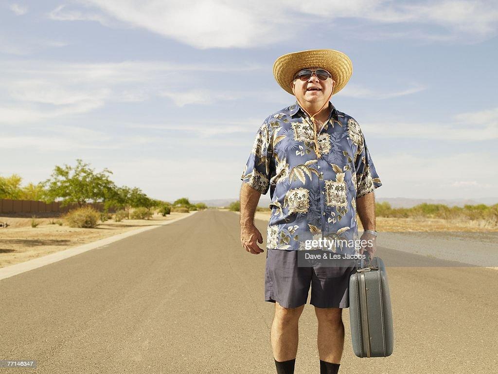 Senior Mixed Race man holding suitcase : Stock Photo