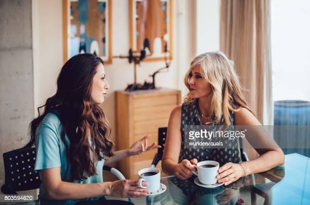 Alta madre e hija tomando café juntos en casa