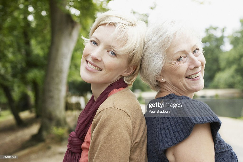 Senior mother and daughter near pond : Stock Photo