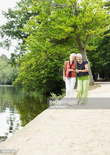 Senior mother and daughter walking near pond