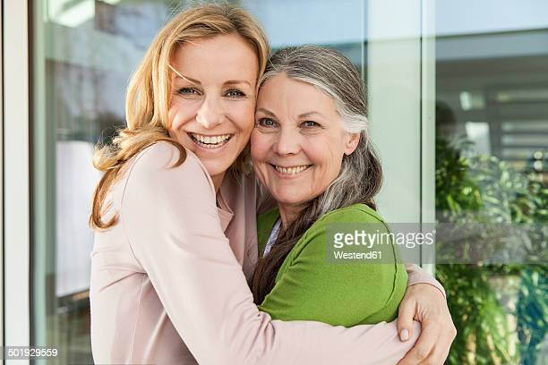 Senior mother and her daughter hugging in front of her house