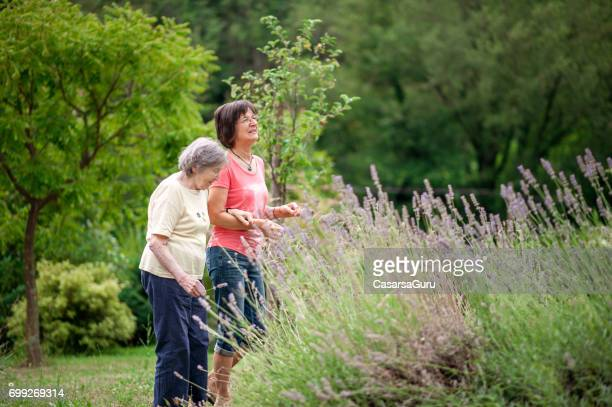 Senior Mother Enjoy The Garden With Her Daughter