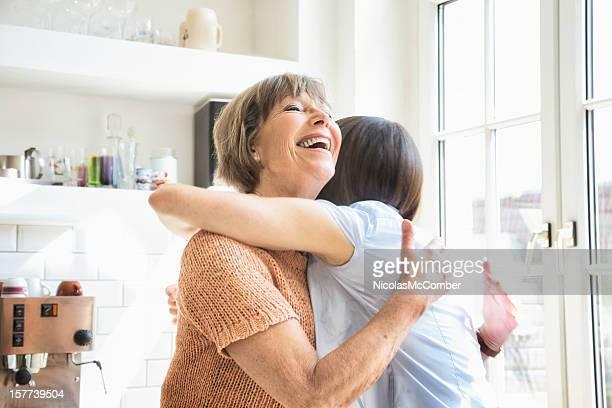 Senior madre riceve un abbraccio di sua figlia felice