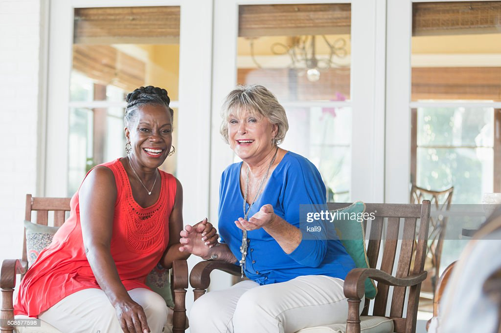 Senior multi-ethnic women sitting on a porch, laughing : Stock Photo