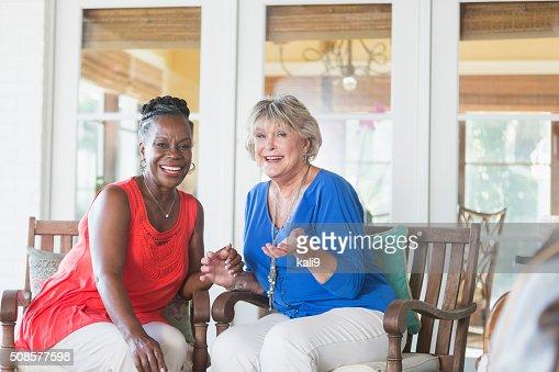 Senior multi-ethnic women sitting on a porch, laughing : Stock Photo