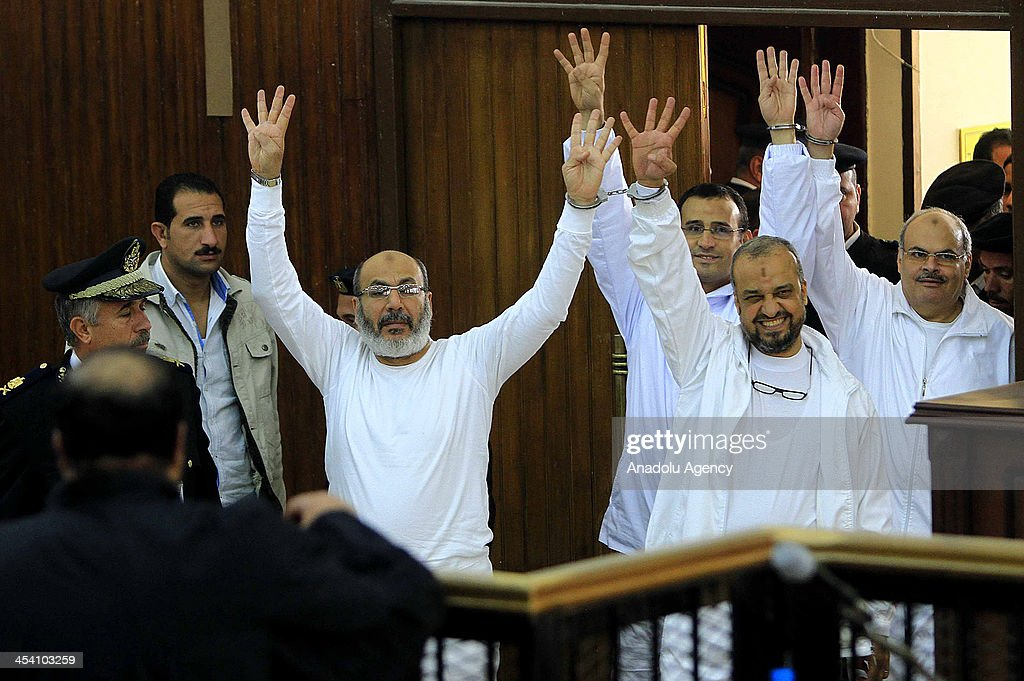 Senior Muslim Brotherhood leader Mohamed El-Beltagy (front R) and Salafist preacher Safwat Hegazy (front L) flash Rabia sign during their trial at Cairo police academy on December 7, 2013 in Cairo, Egypt. The two Islamist leaders, along with two medics, face charges of 'abducting and torturing' two policemen inside the Rabaa al-Adawiya sit-in, the site of a seven-week protest camp in support of ousted president Mohamed Morsi, which was violently dispersed in mid-August and left hundreds of people dead.