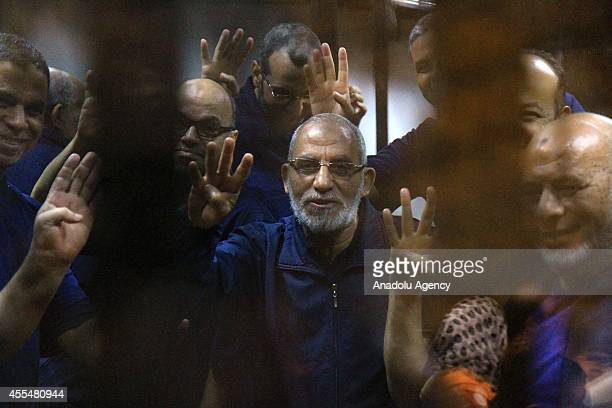Senior Muslim brotherhood leaders and Muslim Brotherhood Supreme Guide Mohamed Badie flash rabia sign during a trial over the Wadi elNatrun prison...