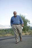 Senior obese man walking on open road, portrait