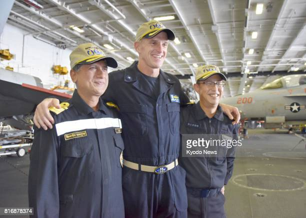 Senior officials of Japan's Maritime SelfDefense Force and the US as well as Indian navies pose for photos on the US aircraft carrier Nimitz during...