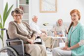Senior on a wheelchair with young nurse