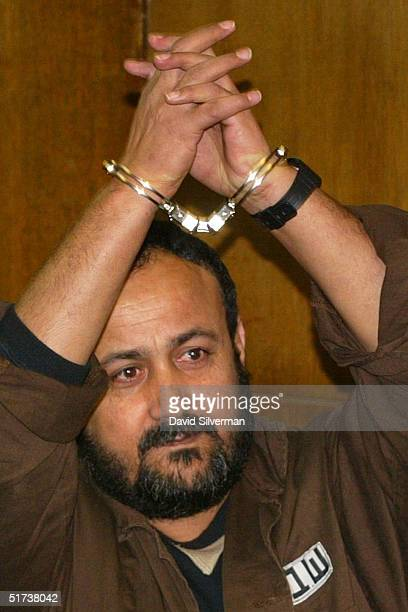 Senior Palestinian activist Marwan Barghouti raises his arms in triumph after he was brought into court January 2 2003 in Tel Aviv Israel A day after...