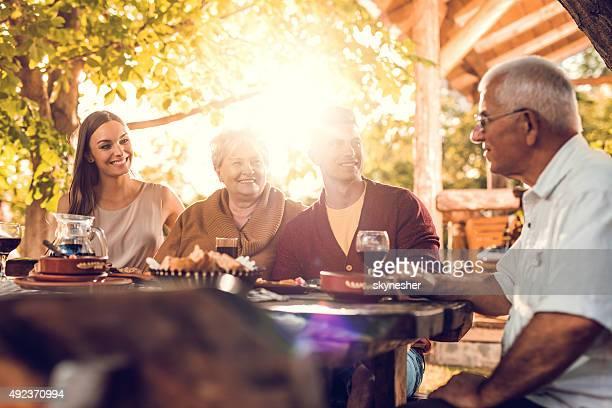 Senior parents communicating with their adult children in restaurant.
