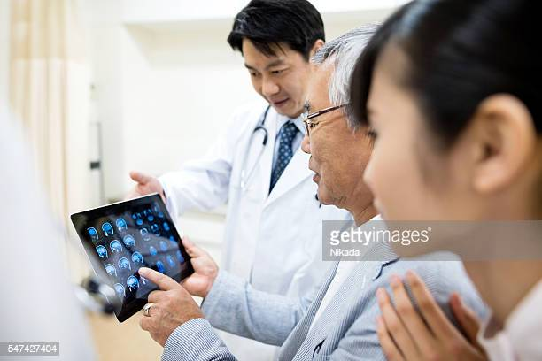 Senior patient and doctor looking at medical results