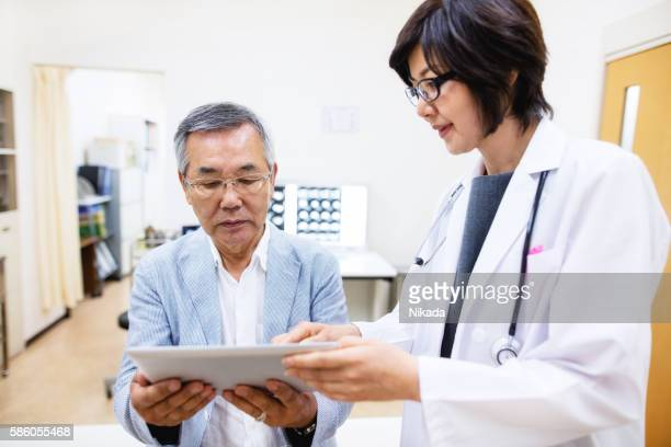 Senior patient and female doctor looking at digital tablet