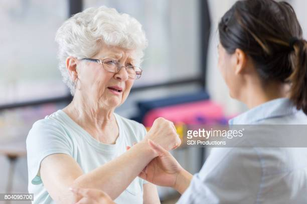 Senior patient grimaces as therapist manipulates elbow