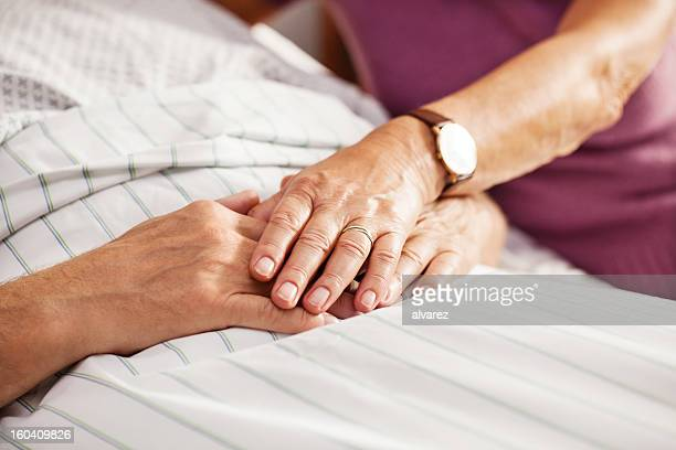 Senior patient holding his wifes hand