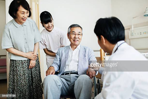 Senior Patient in Wheelchair with Family and Doctor
