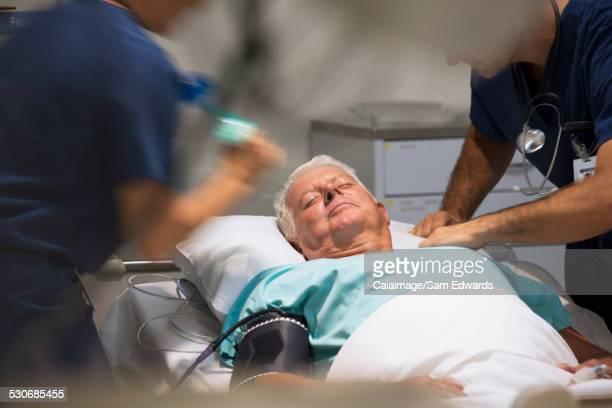 Senior patient receiving medical treatment in intensive care unit