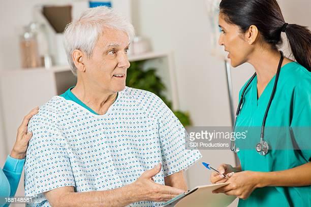 Senior Patienten mit einer Krankenschwester im Krankenhaus reden