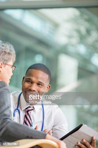 Paziente anziano con giovane medico parlando di risultati dei test