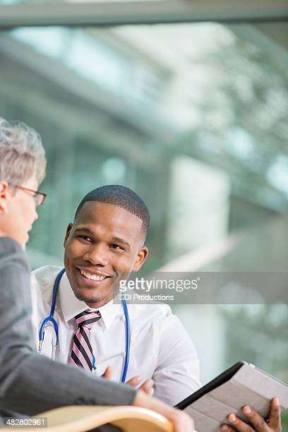 Senior patient talking with young doctor about test results