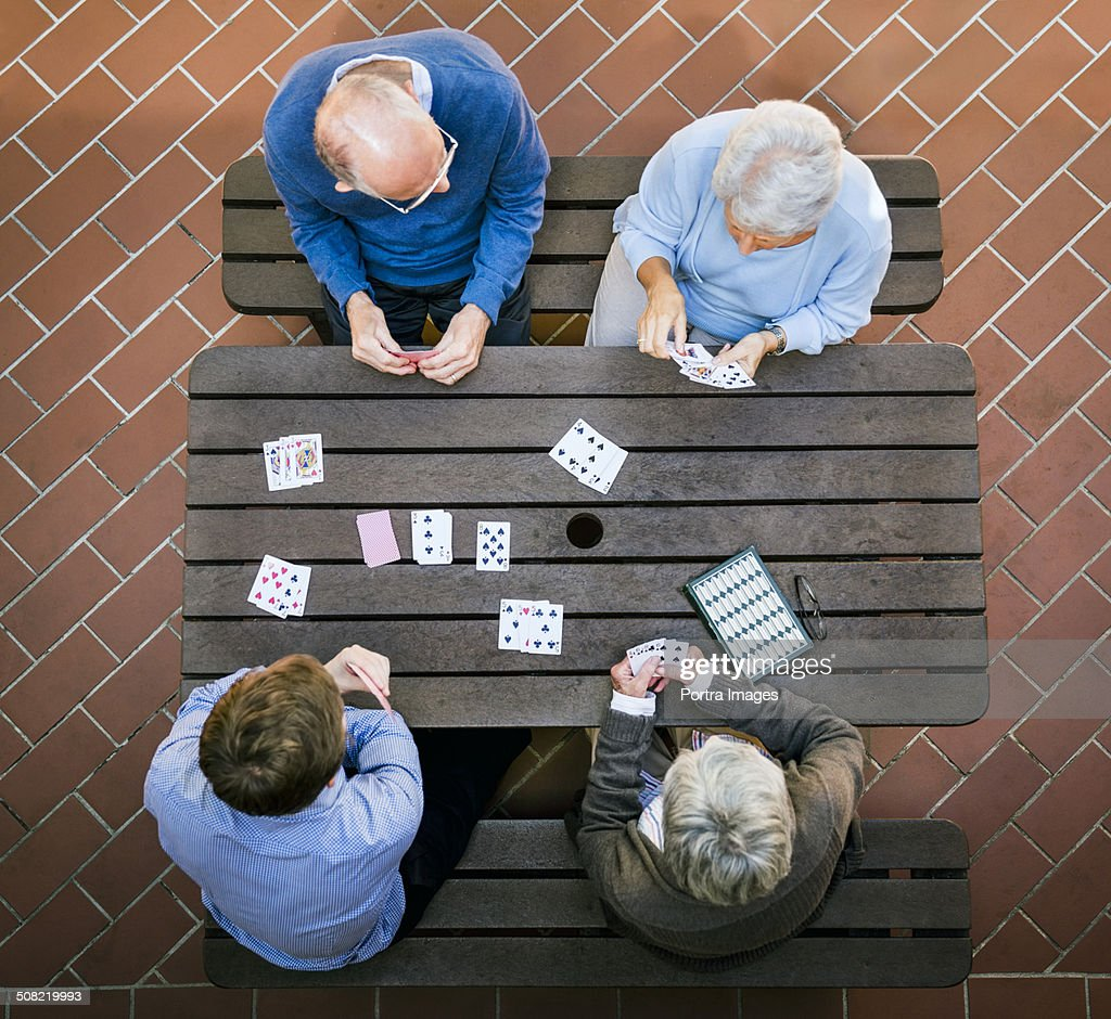 Senior people and caretaker playing cards at table