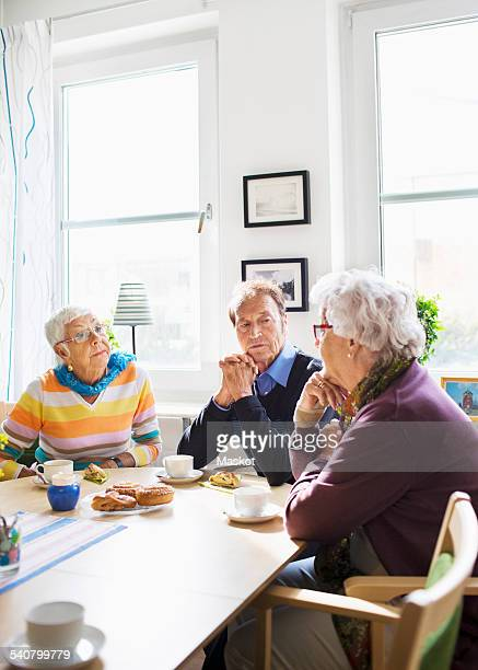 Senior people discussing at breakfast table in nursing home