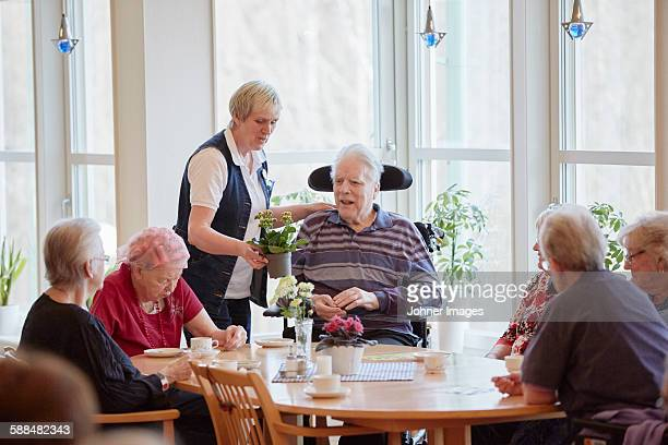 Senior people having coffee in care home