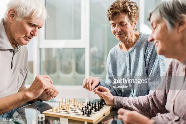 Senior people playing chess.