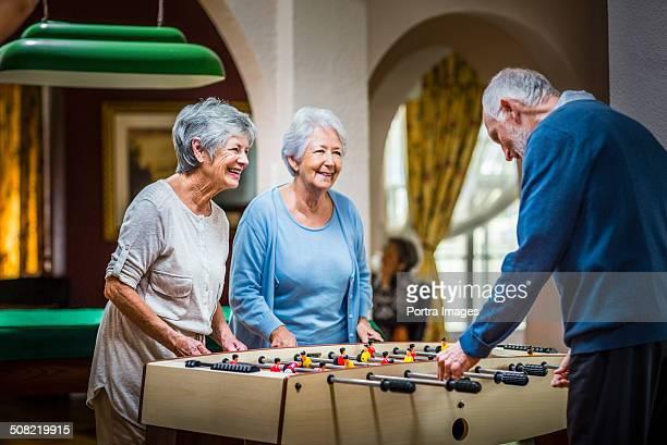 Senior people playing foosball at nursing home