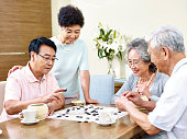 two senior men playing Weiqi (or game of go) at home with their wives watching.