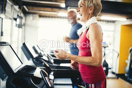 Senior people running in machine treadmill at fitness gym club : Stock Photo