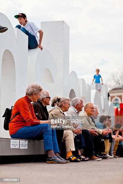 Senior people sitting at IAmsterdam sign