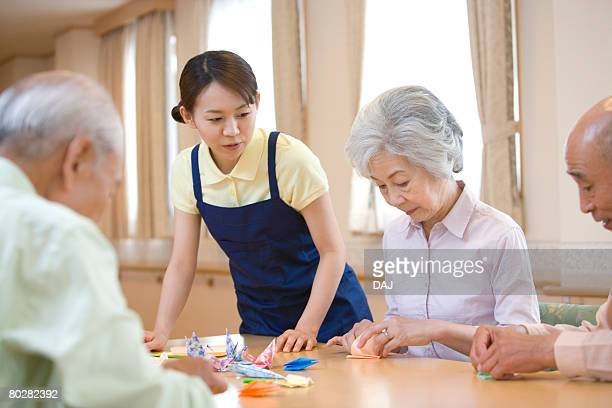 Senior people with nurse making origami cranes in hospital