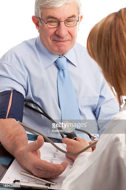 Senior person getting blood pressure examination by a cardiologist