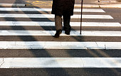 Legs and shadow of a senior person using walking cane while crossing the street in motion blur