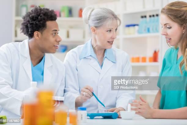 Senior apotheker traint jonge collega's bij samenstelling