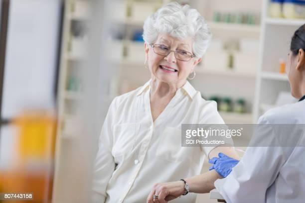 Senior pharmacy customer braces for her flu shot
