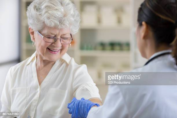 Senior pharmacy customer gets a band-aid after flu shot