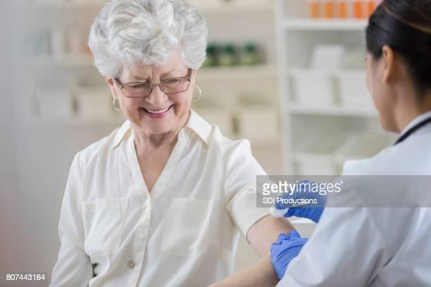 Senior pharmacy customer smiles nervously before flu shot