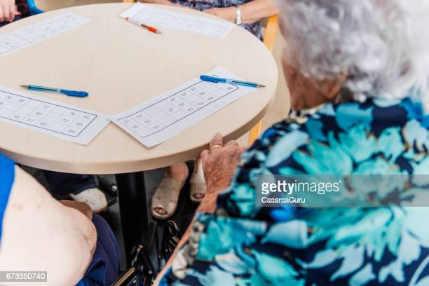 Senior Playing Bingo In The Retirement Home