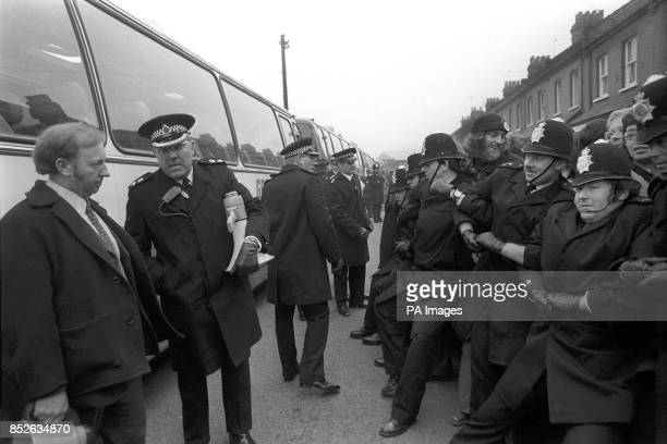A senior police officer talks to yorkshire miners' leader Mr Arthur Scargill as policemen with linked arms struggle to hold back a heaving crowd of...