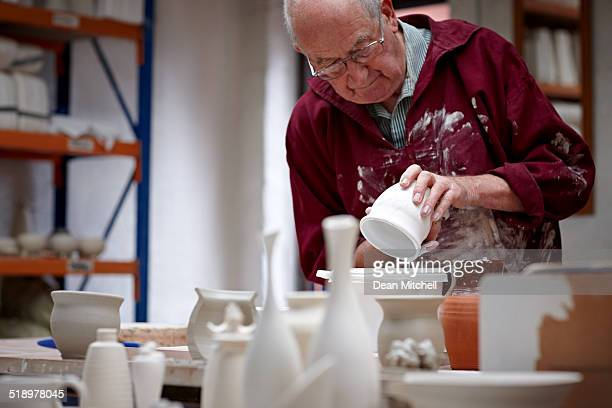 Senior potter painting wet clay pot