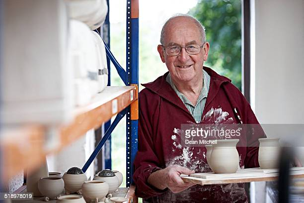 Senior potter with fresh clay pots standing by a shelf