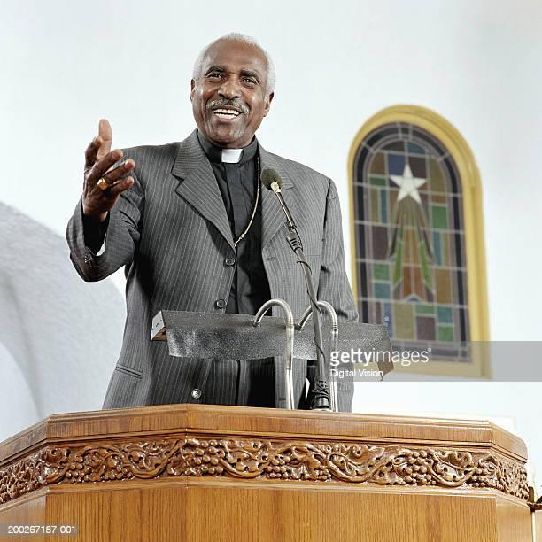 Senior priest giving sermon, smiling, low angle view