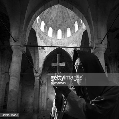 Senior priest in medieval costume praying in church