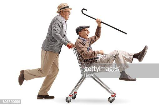 Senior pushing another senior in a shopping cart : Foto de stock