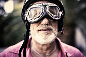 portrait of a senior racing driver wearing vintage helmet and glasses