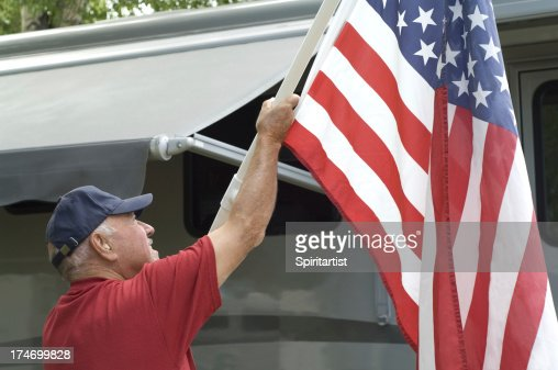 Senior Raising Flag At RV Campground