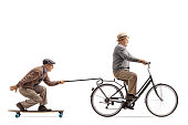 Senior riding a bike with another senior riding a longboard and pulling himself with a cane isolated on white background